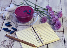 Glass of smoothie, open diary with copy space, honey berries and wild flowers on planks. Morning still life with healthy breakfast. Beautiful summer vintage Royalty Free Stock Photo