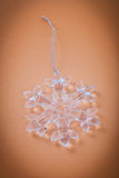 Glass snowflake on brown background Stock Photo