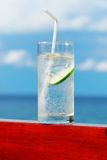 Glass of soda. With lime. Sea in background Royalty Free Stock Images