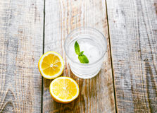 Glass of soda with halved  lemon on wooden table Stock Images