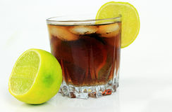 Glass of soda with ice cubes and lime, whiskey cola Stock Image