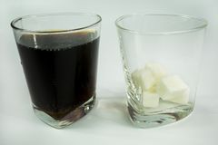 A glass of soda and sugar. How much in a glass of sugar horizon. glass with soda and a glass with refined sugar in cubes on an empty background Stock Photo