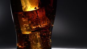 Glass of soda is on the table and bubbles burst out. light from behind. Close up. Glass of soda is on the table and bubbles burst upwards ice cubes cool the stock footage