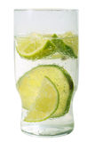 Glass of soda water with cut limes. Glass of soda water with sliced limes in it Royalty Free Stock Photography
