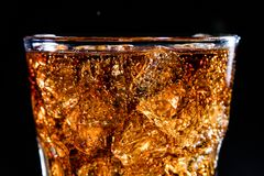 Glass with soft cola drink, ice and bubles. Glass with soft cola drink, ice cubes and bubles royalty free stock images