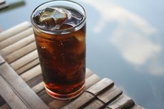 Glass of soft drink on bamboo raft in the lake. Close up Glass of soft drink on bamboo raft in the lake royalty free stock photo