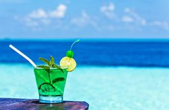 Glass of drink is on a beach table Royalty Free Stock Photos