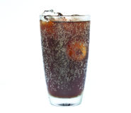 Glass of soft drink. Ice cube splashing into glass of soft drink white background royalty free stock photo