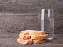 Glass with some water and three pieces of bread Stock Photos