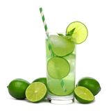Glass of sparkling limeade with limes isolated on white. Glass of sparkling limeade with straw and limes isolated on a white background Stock Photo