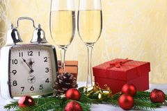 Glass of sparkling shampagne wine, clock, gift box and candles on christmas background. stock image