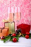 Glass of sparkling shampagne wine, clock, gift box and candles on christmas background. royalty free stock image