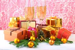 Glass of sparkling shampagne wine, clock, gift box and candles on christmas background. stock photos