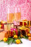 Glass of sparkling shampagne wine, clock, gift box and candles on christmas background. stock photo