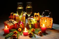 Glass of sparkling shampagne wine, clock, gift box and candles on christmas background. royalty free stock images