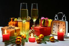 Glass of sparkling shampagne wine, clock, gift box and candles on christmas background. royalty free stock photo