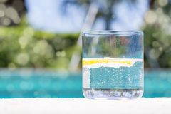 Glass of sparkling water with lemon. On the pool nosing at the tropical resort. Horizontal, glass on the right side. Bokeh details Stock Photo