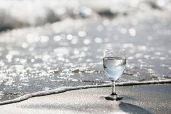 A glass of sparkling water on a sandy beach on a bright day.Style sepia tone. A glass of wine on the waxing background of soft drinks on the beach on a bright royalty free stock photos