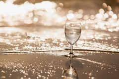 A glass of sparkling water on a sandy beach on a bright day.Style sepia tone. A glass of wine on the waxing background of soft drinks on the beach on a bright stock image