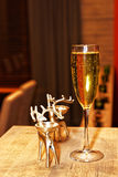 Glass of sparkling wine and candlestick in reindeer form Royalty Free Stock Photo