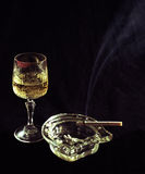 Meeting. A glass of sparkling wine smoldering cigarette in the ashtray isolated black background Stock Photos