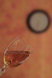 Glass of sparkling wine. Glass of white wine on a background with a blurred image of a clock.  Alcohol can make you disoriented and can make you losing the sense Stock Photography