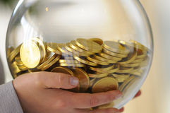 Glass sphere with coins Stock Images