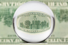 Glass sphere, dollar, three. Hundred dollar banknote through glass sphere. Blur background Royalty Free Stock Images