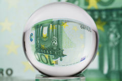 Glass sphere, euro, one. Hundred euro banknote through glass sphere. Blur background Stock Image