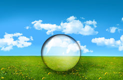 Glass sphere in a field of  grass Stock Photos