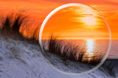 Glass sphere reflecting orange sunset Royalty Free Stock Photo