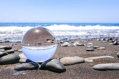 Glass sphere on stones at beach in Madeira Stock Photography