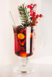 Glass of spiced mulled wine with berries and fir branch Royalty Free Stock Photos