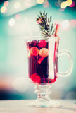 Glass of spiced mulled wine with berries and fir branch on table at bokeh lighting background Stock Photos