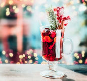 Glass of spiced mulled wine with berries and fir branch on table at festive bokeh lighting Stock Photography
