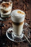 A glass of spicy latte with whipped cream and cinnamon, standing on a brown board. Coffee beans. Dark background stock photos