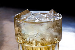 Glass of spirits with ice on the rock. dark background Royalty Free Stock Image