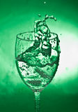Glass with splash on green background Royalty Free Stock Photography