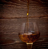 The glass with splashes brandy Stock Photos