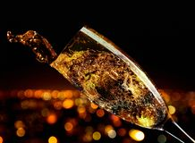 Glass of splashing champagne. On a background of night city royalty free stock images