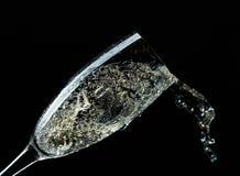 Glass of splashing champagne isolated on black. Background stock photography