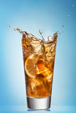 Glass of splashing iced tea with lemon Royalty Free Stock Photos