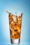 Glass of splashing iced tea with lemon Royalty Free Stock Photos