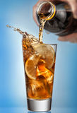 Glass of splashing iced tea with lemon on blue background Stock Photo