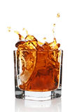 Glass with splashing whisky drink Royalty Free Stock Photography