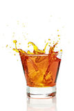 Glass with splashing whisky drink Stock Images