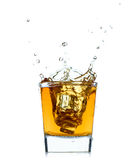 Glass with splashing whisky drink on white background. Royalty Free Stock Photo