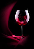 Glass of splashing wine with red silk Royalty Free Stock Photos