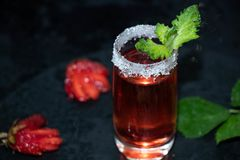 A glass is sprinkled with sugar, there is a strawberry tincture inside royalty free stock photos
