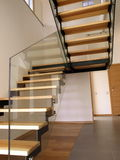 Glass staircase. Glass, wooden and metal staircase in a modern interior stock image